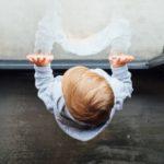 窓に手をついて立っている赤ん坊の写真
