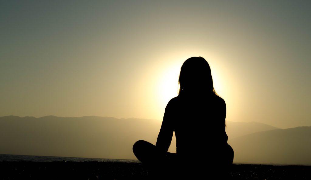 太陽に向かって瞑想する人物