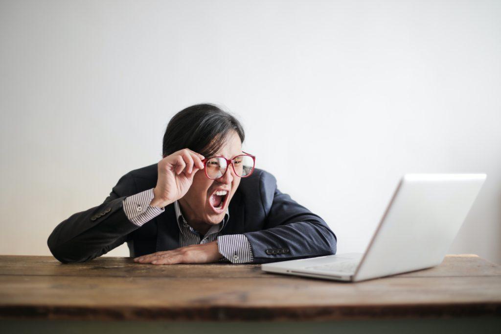モニタを見て叫んでいる男性の写真